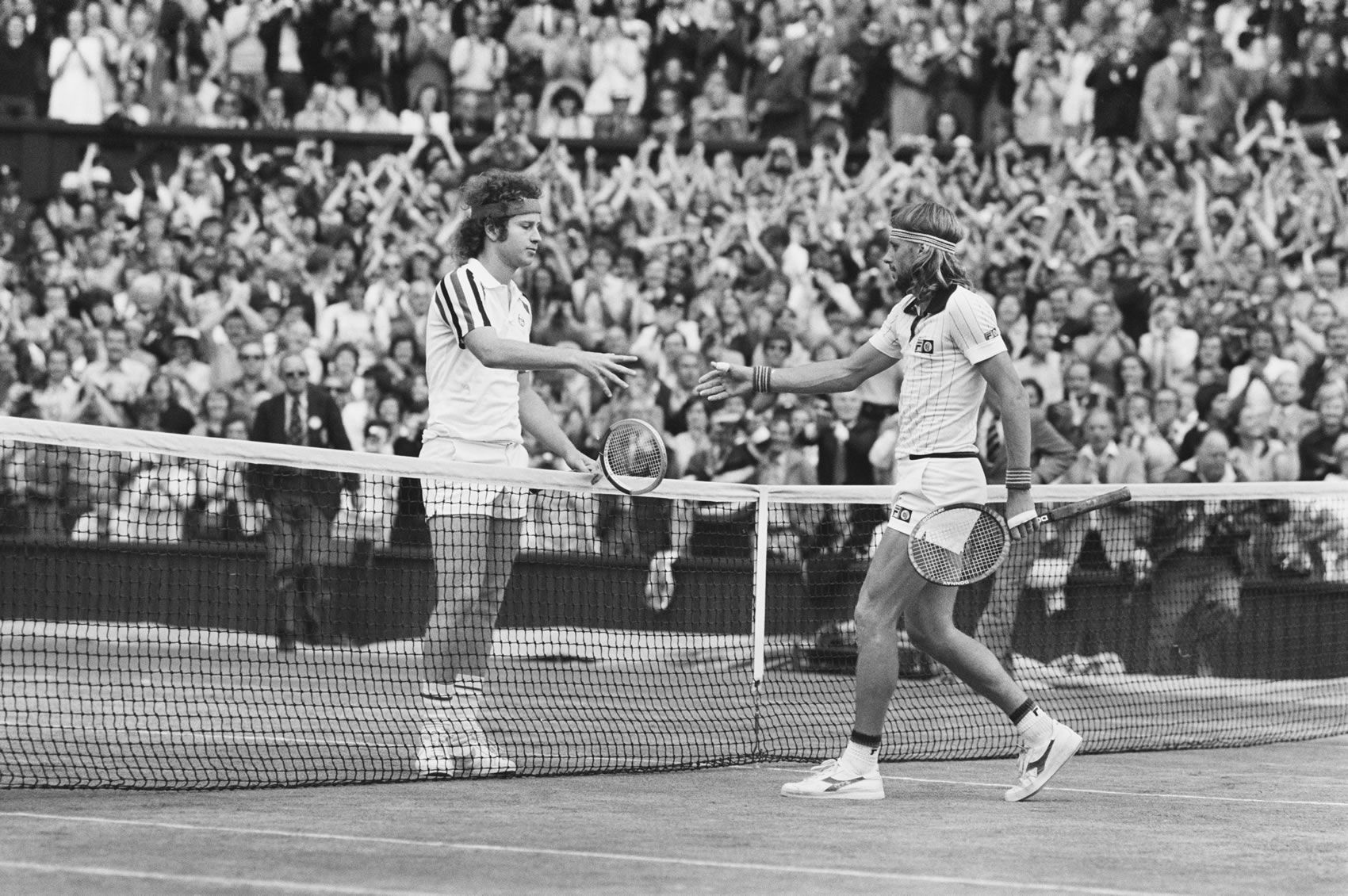 Björn Borg and John McEnroe Swedish tennis player Bjorn Borg (right) shakes hands over the net with American tennis player John McEnroe after winning the final of the Men's Singles tournament, 1-6, 7-5, 6-3, 6-7, 8-6 to become champion at the Wimbledon Lawn Tennis Championships at the All England Lawn Tennis Club in Wimbledon, London on 5th July 1980. (Photo by Chris Smith/Popperfoto/Getty Images)