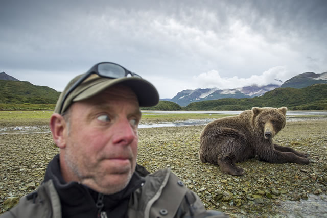 Paul Souders grimacing as Brown Bear (Ursus arctos) sits nearby along salmon spawning stream Image courtesy of Paul Souders - Copyright Paul Souders©